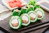 Salmon sushi rolls covered with chuka seaweed