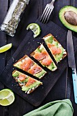 Sandwich with avocado and smoked salmon on a black wooden board