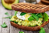 Grilled sandwich with avocado, poached egg and arugula on wooden table