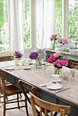 Gedeckter Tisch mit mehreren Hortensiensträußen im Wintergarten