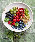 Mix of fresh berries with leaves in vintage ceramic colander on green rustic wooden background