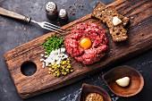 Beef Tatar mit Ei auf rustikalem Holzuntergrund