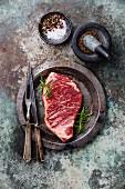 Rohes Striploin Steak und Gewürze im Mörser auf Metalluntergrund