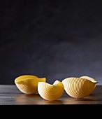Three pieces of uncooked conchiglie pasta with a dark background