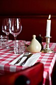 A dinner table set with a checked tablecloth, glasses and candlestick
