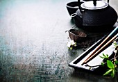 A Chinese tea set, chopsticks and a sakura branch on rustic wooden table