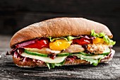 Sandwich with chicken, cheese and vegetables on a rustic background