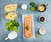 Zutaten für Nudelgericht: Tagliatelle, Lachs, Spinat und Sahne auf grauem Hintergrund