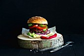 Fresh homemade burger on wooden serving board with red chili peppers over black background