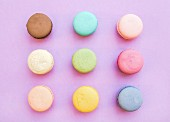 Sweet colorful French macaron biscuits on pastel pink background