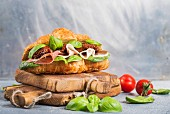 Croissant sandwich with smoked meat Prosciutto di Parma, sun dried tomatoes, fresh spinach and basil on stone background