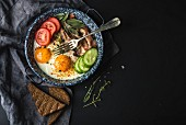 Pan of fried eggs with bacon, fresh tomato, cucumber, sage and bread on dark serving board over black background