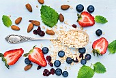 Healthy breakfast ingredients: Oatmeal, berries, almond and mint leaves on painted blue wooden background
