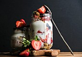 Yogurt oat granola with strawberries, mulberries, honey and mint leaves in tall glass jar on black backdrop