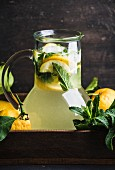 Homemade lemonade with mint and ice, served with fresh lemons in wooden tray