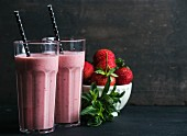 Strawberry and mint smoothie in tall glasses, bawl of fresh berries on dark rustic wood background