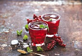 Limonade aus roten Johannisbeeren mit Eis und Minze auf Vintage Metalluntergrund