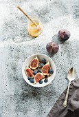 Healthy breakfast: Bowl of oat granola with yogurt, fresh blueberries and figs