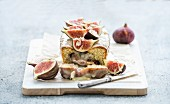 Loaf cake with figs, almond and white chocolate on white serving board