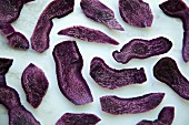 Purple potatoes, cut in to chips on a white marble background