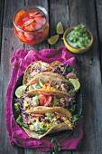 Tacos with pork, fermented vegetables and an avocado and coriander sauce