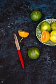 Various citrus fruits on a plate with a knife next to it