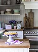 Cheese Cake dekoriert mit Blüten auf Kuchenständer in Landhausküche