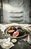 A still life with figs, thyme, goat's cheese and honey
