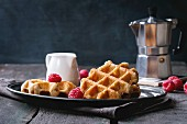 Belgian waffles with raspberries, served with coffee pot and jug of milk