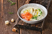 Bowl of white asparagus cream soup with pea sprouts, salted salmon and toast
