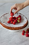 Almond cake topped with fresh strawberries on white stand, gluten-free
