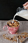 Almonds and cranberries homemade granola in a cup with milk pouring from a jar