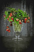 Bunch of ripe wild strawberries with leaves in vintage glass over old metal background