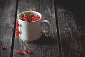Old white cup full of fresh ripe red currant over old wooden table