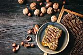 Honigwabe auf Keramikteller und verschiedene Nüssen auf altem Holztisch