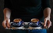 A woman serving two cups of Turkish coffee on a silver tray