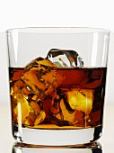 A glass of whiskey with ice cubes (close-up)