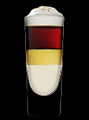 A layered drink with eggnog against a black background