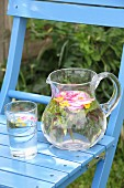 Wasser mit Kräutern und Blüten im Glas und Glaskrug