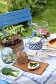 Gedeckter Tisch mit Dinkel-Roggen-Hausbrot, Quarkbällchen, Quarkaufstrich und Käsekuchen