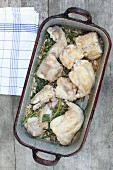 Rabbit in a roasting tin with shallots, garlic, herbs and pine nuts