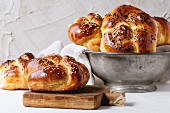 Heap of sweet round sabbath challah bread with white and black sesame seeds in vintage metal bowl