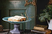 Old wooden Christmas table with big plate of Butter cream Eclairs, decorating by Christmas stars, tree and vintage books