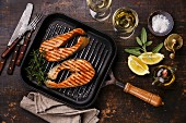 Grilled salmon Steak on grill pan on wooden background with wine