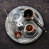 Turkish coffee in coffee pot and cold water on silver tray on black stone background