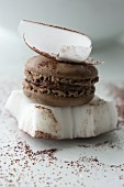 A chocolate macaron between two pieces of coconut