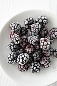 Frozen blackberries on a white plate