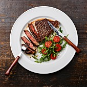 Sliced medium rare grilled Beef steak Striploin and salad with tomatoes and arugula on white plate