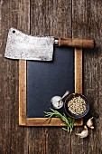 Vintage slate chalk board, Butcher meat cleaver and spices on wooden background