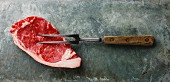 Raw fresh meat steak Striploin and meat fork on gray stone slate background